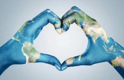 Female hands, painted in the world map, forming heart shape isolated on blue background